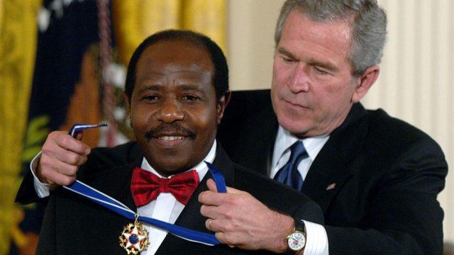 Paul Rusesabagina being handed a medal by US former president George Bush . (KT press)